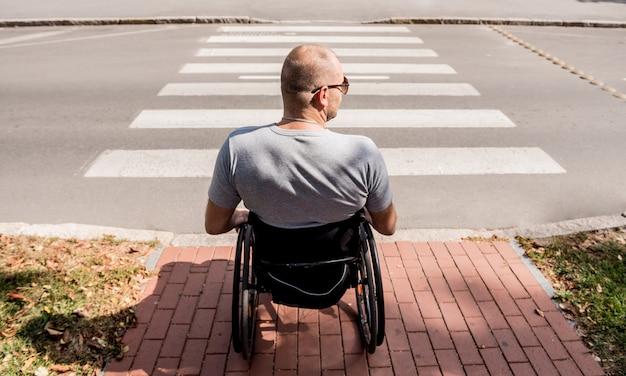 Homem com deficiência em cadeira de rodas se preparando para atravessar a rua na faixa de pedestres