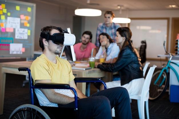 Homem com deficiência física em cadeira de rodas usando fone de ouvido vr no escritório