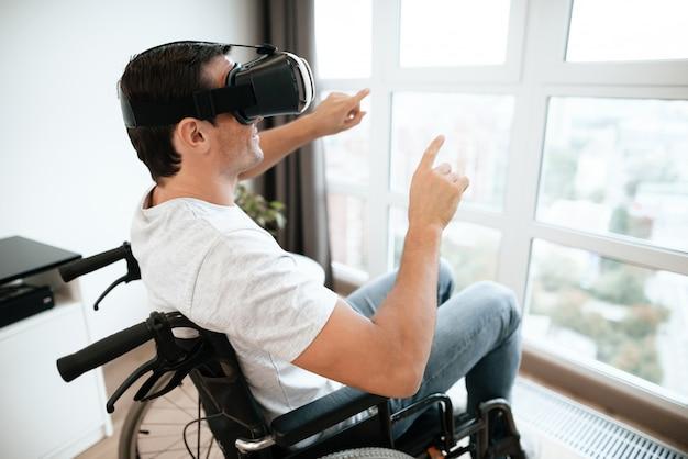 Homem com deficiência gosta de óculos de realidade virtual com as mãos para cima.