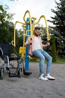 Homem com deficiência na máquina de exercício no parque. pessoas paralisadas e dificuldades com deficiências, superação de deficiências. pessoa do sexo masculino com deficiência em campo esportivo