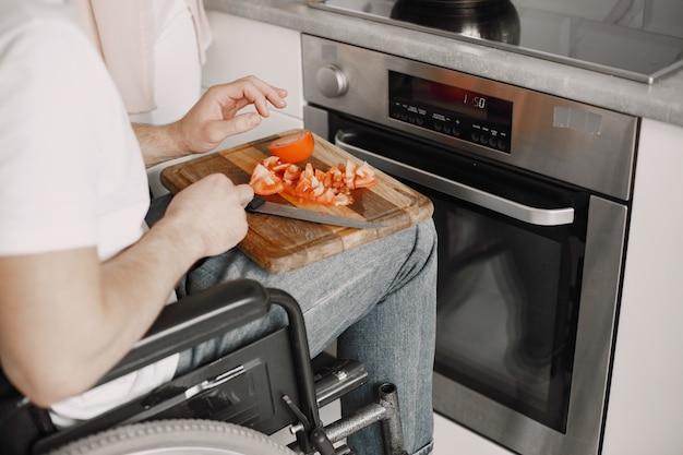 Homem com deficiência que prepara alimentos na cozinha. cortar vegetais.