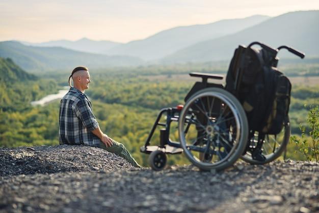 Homem com deficiência sentado na montanha perto de cadeira de rodas e as mãos levantadas, apreciando o ar fresco e a beleza da natureza.