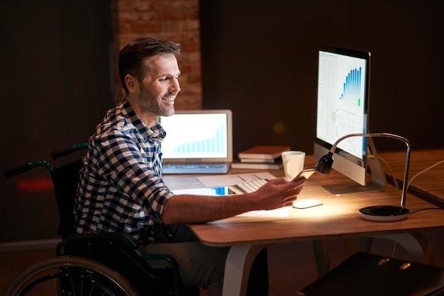 Homem com deficiência trabalhando com tecnologia à noite
