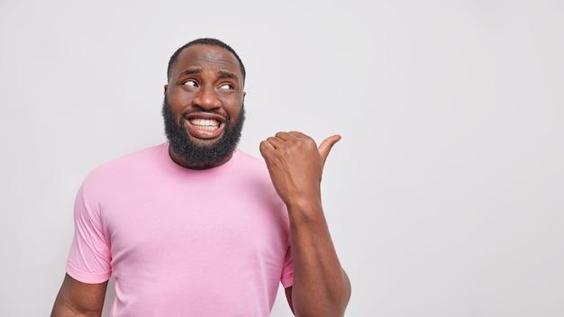 Homem com dentes brancos aponta o polegar para longe em um espaço em branco mostra o lugar para o logotipo ou colocação de produto vestido com uma camiseta rosa casual