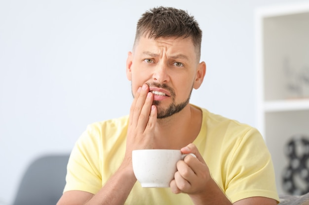 Homem com dentes sensíveis e café quente em casa