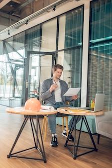 Homem com desenho sentado à mesa no trabalho