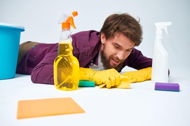Homem com detergente limpando o apartamento prestação de serviços