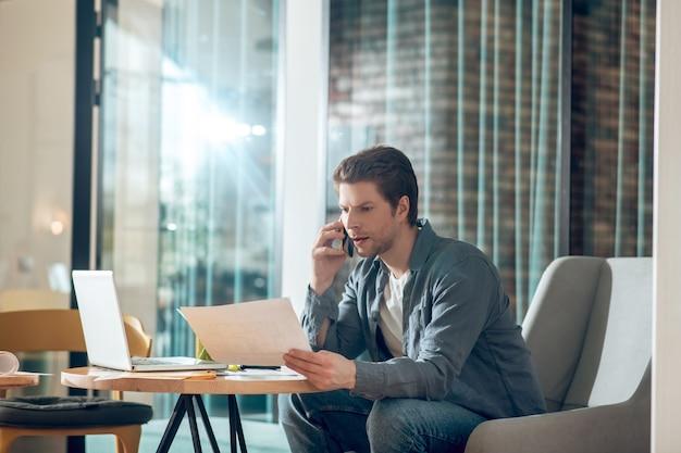 Homem com documento falando no smartphone