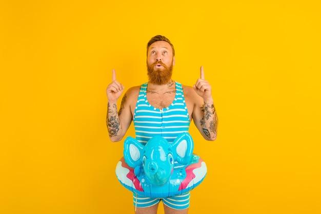 Homem com donut inflável com elefante pronto para nadar