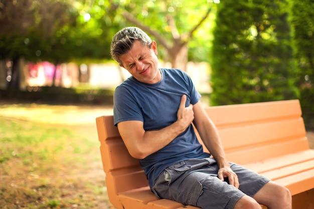 Homem com dor de coração ao ar livre. masculino, sentindo dor no peito, sentado no banco do parque. conceito de saúde e medicina