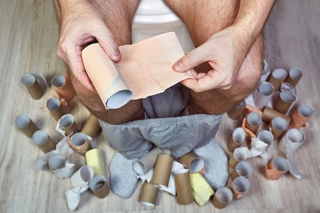 Homem com dor de estômago devido a disenteria ou disbiose está sentado no vaso sanitário do banheiro, com um pedaço de papel higiênico nas mãos, cercado por mangas de papelão.