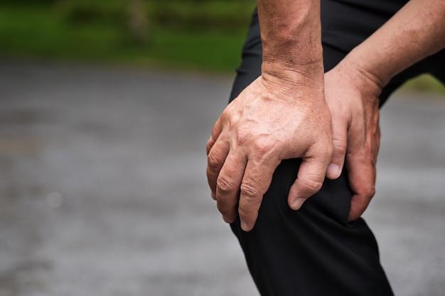 Homem com dor nas articulações do joelho artrite inflamação asiático sênior ou meia-idade