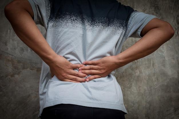 Homem com dor nas costas. alívio da dor e conceito de cuidados de saúde.