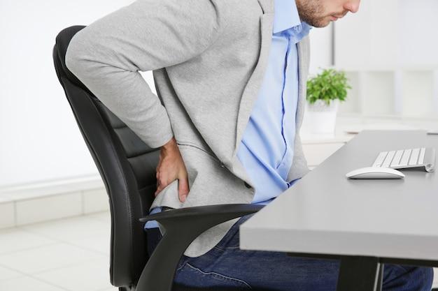 Homem com dor nas costas numa poltrona no escritório, closeup