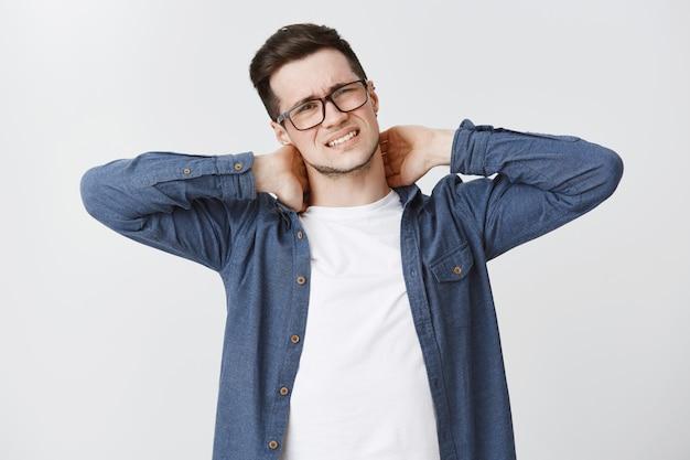 Homem com dor no pescoço, fazendo caretas e reclamando