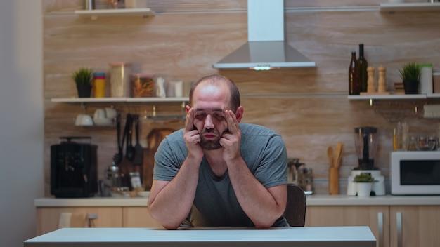 Homem com dores de cabeça, sentado na cozinha, massageando as têmporas. estressado, cansado, preocupado, doente, com enxaqueca, depressão, doença e ansiedade, sentindo-se exausto com sintomas de tontura.