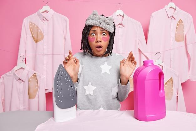 Homem com dreadlocks parece aterrorizado perto de tábua de passar roupa com um frasco de detergente químico ocupado fazendo tarefas domésticas