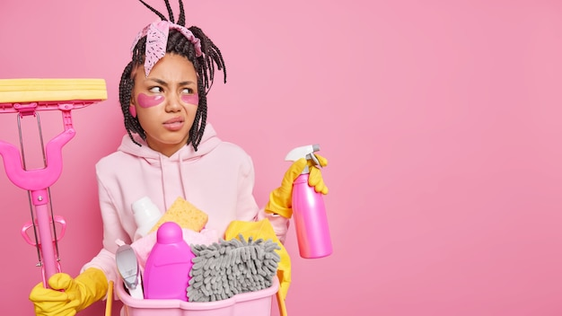 Homem com dreads segurando spray de detergente e esfregão com sorriso afetado no rosto rosa