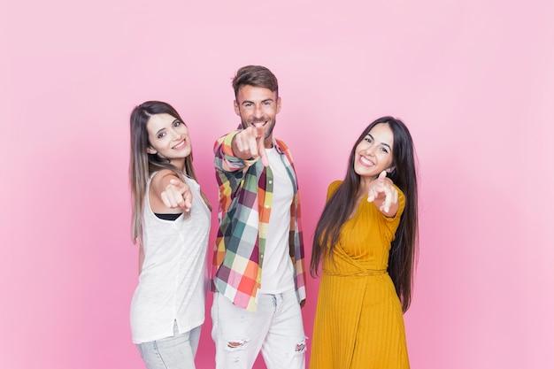 Homem com duas amigas apontando o dedo para a frente contra um fundo rosa