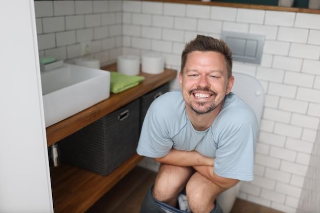 Homem com emoção de alívio sentado no banheiro