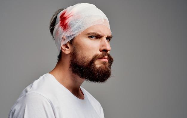 Homem com enfaixamento na cabeça e no braço, problema de tratamento com sangue, lesão no hospital