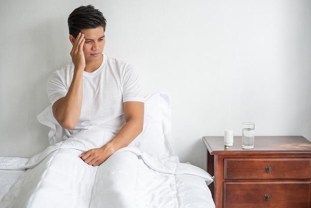 Homem com enxaqueca, mão tocando a cabeça, sentado na cama.