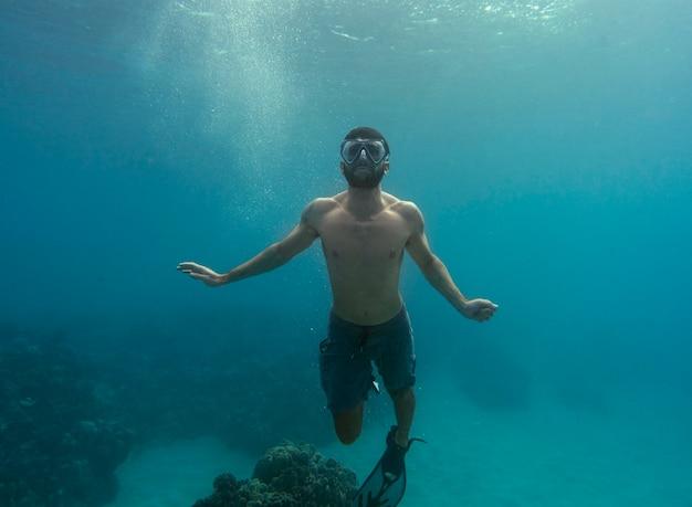 Homem com equipamento de mergulho nadando no oceano