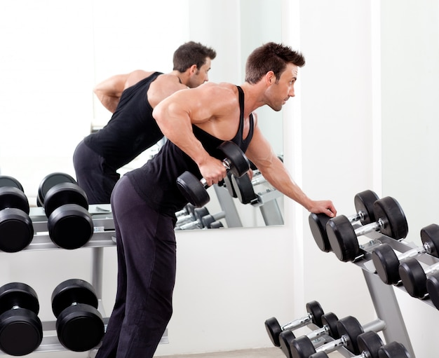 Homem com equipamento de treinamento de peso no ginásio de esporte