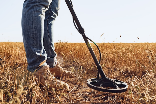 Homem com equipamento detector de metais em busca de produtos de metal no campo