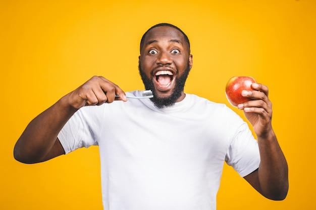 Homem com escova de dente. imagem de jovem africano sem camisa, segurando uma escova de dentes com creme dental e maçã, sorrindo