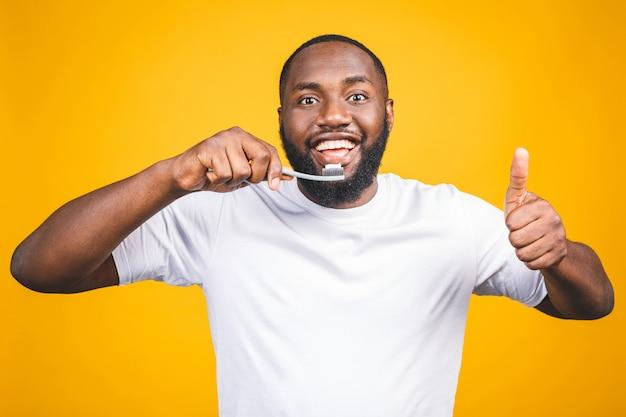 Homem com escova de dente. imagem de jovem africano sem camisa, segurando uma escova de dentes com creme dental e sorrindo polegares para cima.