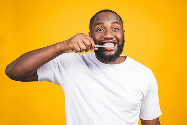 Homem com escova de dente. imagem de jovem africano sem camisa, segurando uma escova de dentes com creme dental e sorrindo
