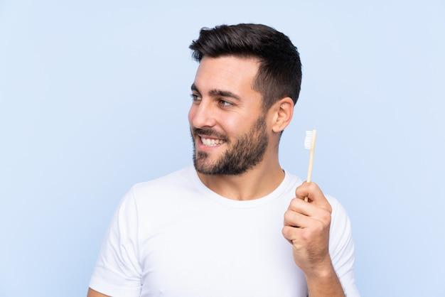 Homem com escova de dentes na parede azul isolada