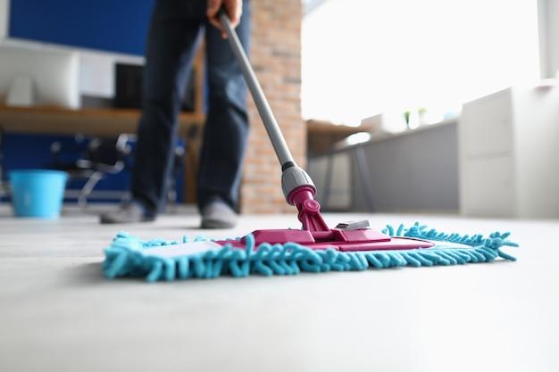 Homem com esfregão lava chão no escritório. conceito de serviços de empresa de limpeza