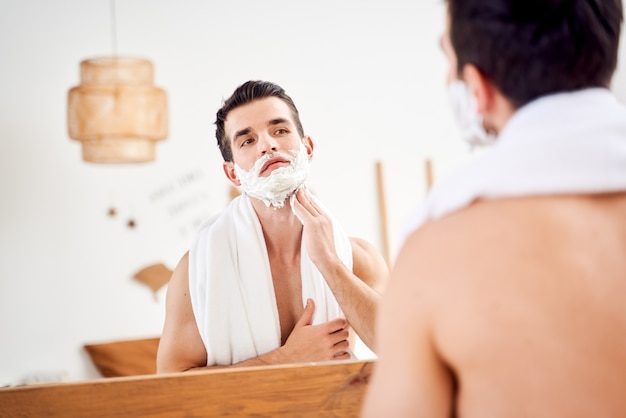 Homem com espuma na barba perto do espelho pela manhã