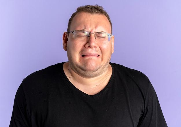 Homem com excesso de peso, de óculos, chateado, com uma camiseta preta e um rosto infeliz que vai chorar em pé sobre uma parede azul