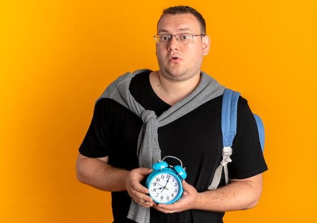 Homem com excesso de peso de óculos, usando uma camiseta preta, segurando um despertador, parecendo surpreso em pé sobre uma parede laranja