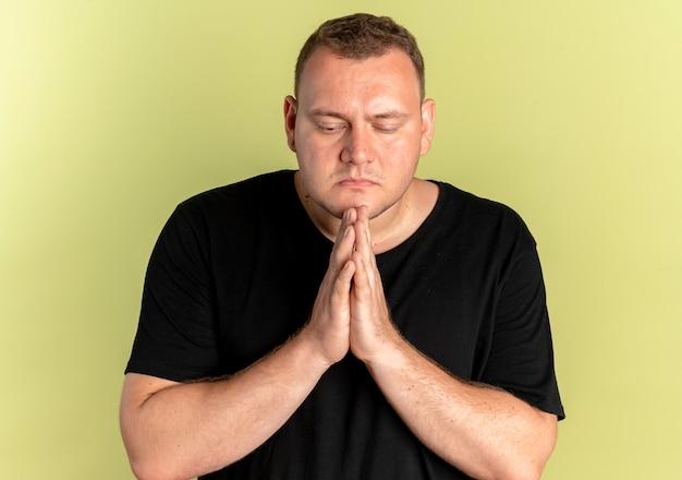 Homem com excesso de peso de óculos, vestindo uma camiseta preta de mãos dadas como se estivesse orando com expressão de esperança sobre a luz