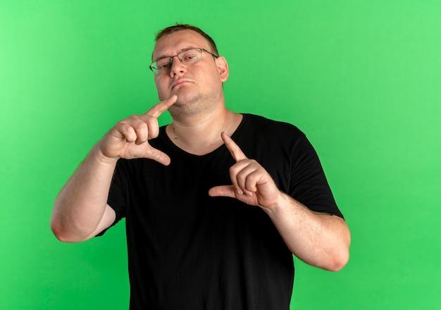Homem com excesso de peso de óculos, vestindo uma camiseta preta, fazendo uma moldura com os dedos parecendo confiante em pé sobre a parede verde