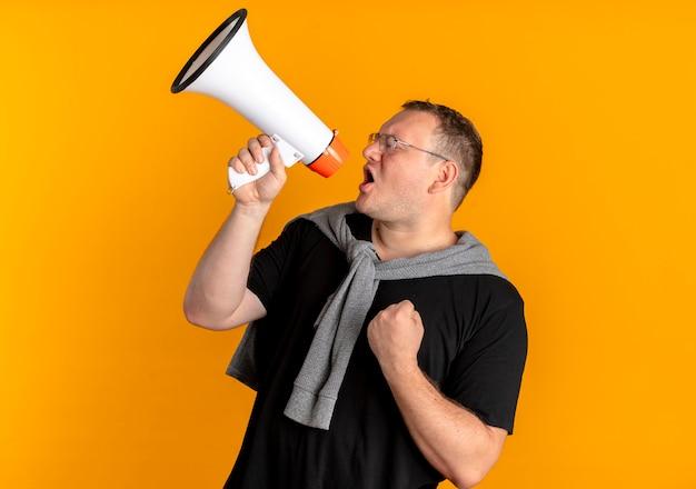 Homem com excesso de peso de óculos, vestindo uma camiseta preta, gritando para o megafone com o punho cerrado em pé sobre a parede laranja