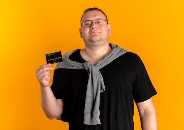 Homem com excesso de peso de óculos, vestindo uma camiseta preta mostrando o cartão de crédito, olhando para a câmera com um sorriso no rosto em pé sobre uma parede laranja