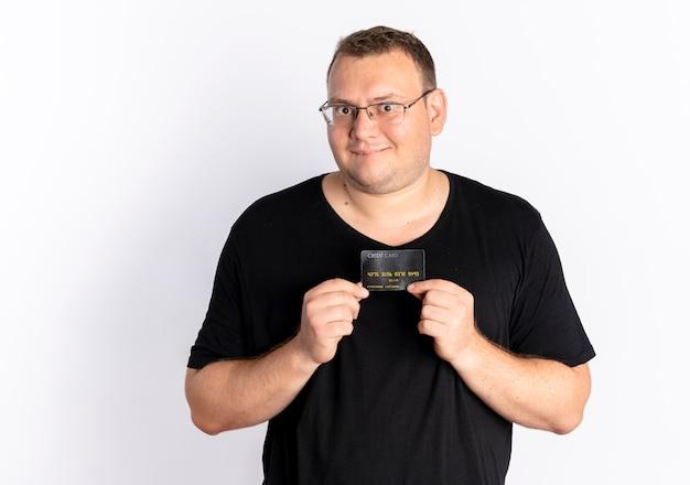 Homem com excesso de peso de óculos, vestindo uma camiseta preta mostrando o cartão de crédito, olhando para a câmera com uma cara feliz em pé sobre uma parede branca