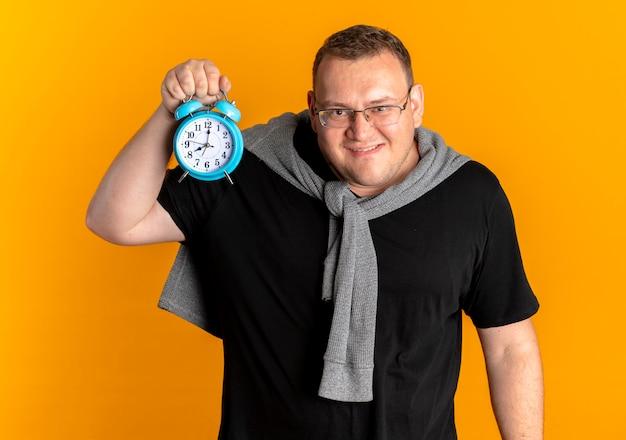 Homem com excesso de peso de óculos, vestindo uma camiseta preta mostrando o despertador olhando para a câmera e sorrindo maliciosamente em pé sobre uma parede laranja