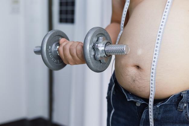 Homem com excesso de peso fazendo exercícios levantando peso com halteres