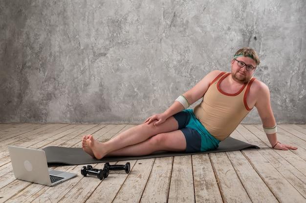 Homem com excesso de peso se exercitando, fazendo exercícios de alongamento na esteira de ioga, assistindo a vídeos de fitness online no laptop em casa.