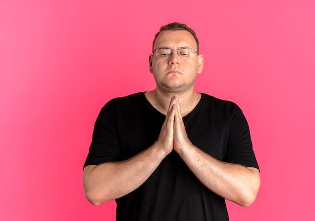 Homem com excesso de peso usando óculos e camiseta preta segurando as palmas das mãos juntas como se estivesse orando com expressão de esperança sobre o rosa