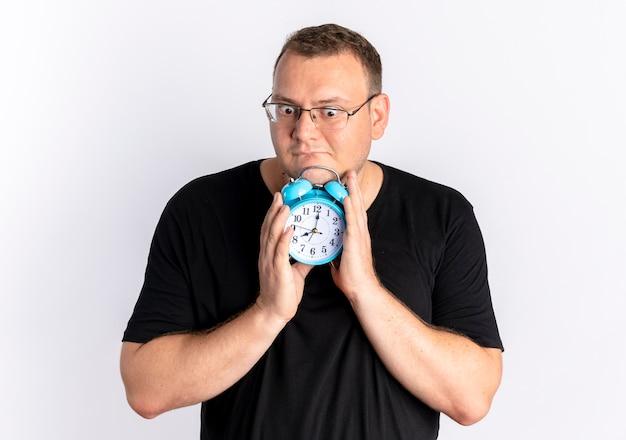 Homem com excesso de peso usando uma camiseta preta de óculos segurando um despertador e parecendo perplexo em pé sobre uma parede branca
