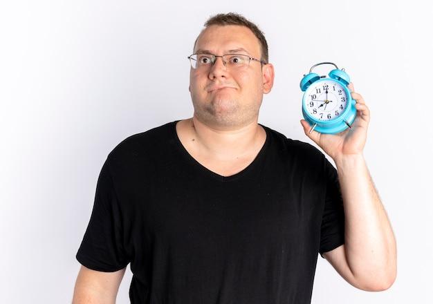 Homem com excesso de peso vestindo camiseta preta com óculos, segurando um despertador, parecendo confuso em pé sobre uma parede branca