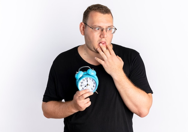 Homem com excesso de peso vestindo camiseta preta de óculos, segurando o despertador cobrindo a boca com a mão, levando um choque em pé sobre uma parede branca