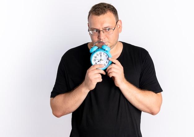 Homem com excesso de peso vestindo uma camiseta preta de óculos segurando um despertador olhando para o lado com uma expressão triste em pé sobre uma parede branca